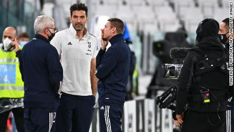 Juventus goalkeeper Gianluigi Buffon talks with staff members ahead of the scheduled match.