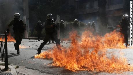 Riot policemen try to avoid flames from a petrol bomb thrown by protesters on Wednesday.