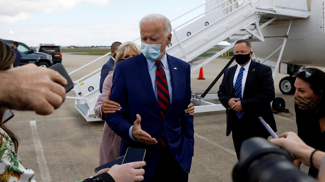 Biden is reminded by his wife, Jill, to maintain proper social distancing as he speaks to reporters at an airport in Miami in October 2020.