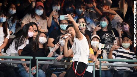 Singer Eric Chou takes a selfie with masked members of the audience while performing in a concert in Taipei, Taiwan, on August 9, 2020.