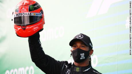 Lewis Hamilton holds aloft a helmet worn by Michael Schumacher after he tied the German legend's F1 win record at the Eifel GP.
