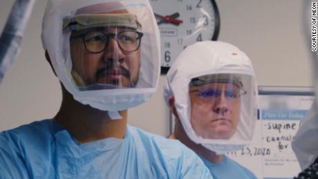 Le personnel médical est représenté portant des écrans faciaux dans `` Totalement sous contrôle ''.  (Gracieuseté de Neon)