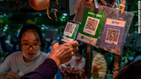 A Chinese customer using his phone to pay via a QR code with the WeChat app at a market in September in Beijing.