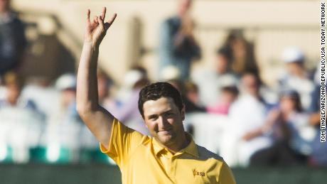 Rahm gives the pitchfork salute after finishing his round at 12-under par.