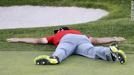 Rahm lies on the green of the 18th hole after winning the Farmers Insurance Open in 2017.