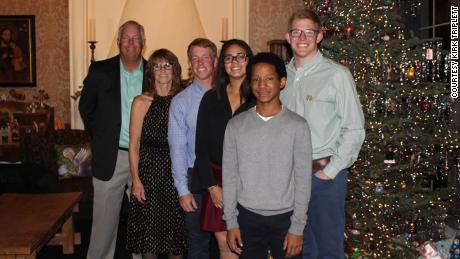 The Triplett family is pictured in an old Christmas photo, from left: Kirk with his wife Cathi, son Sam, adopted daughter Lexy, adopted son Kobe, and son Conor.