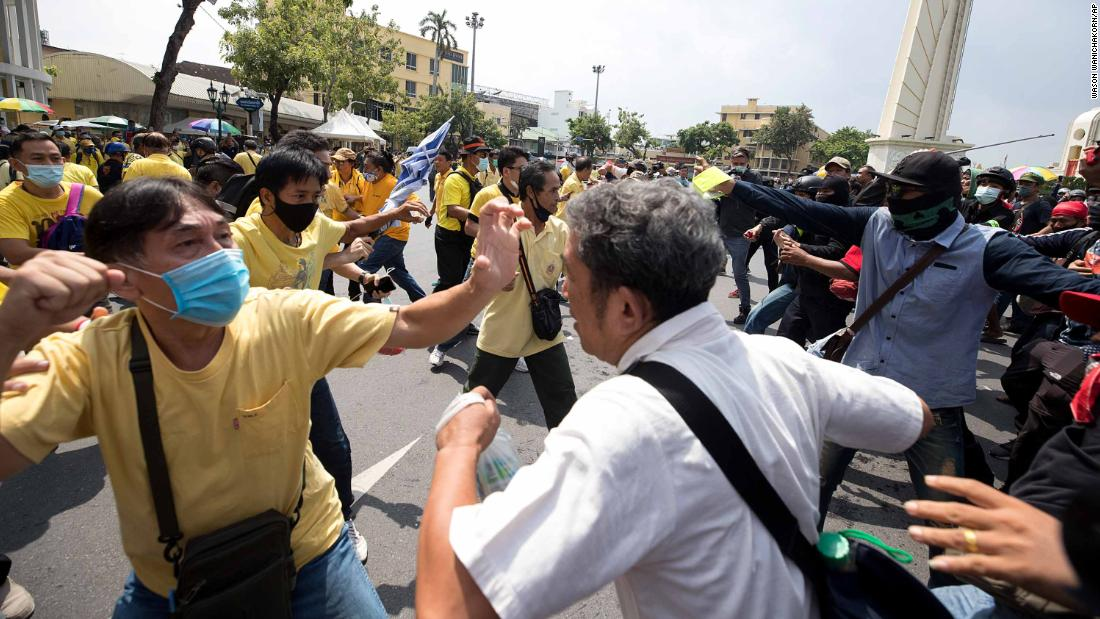 A pro-democracy protester, right, and and a supporter of the monarchy, in yellow, exchange blows at a rally near the Democracy Monument in Bangkok on October 14.