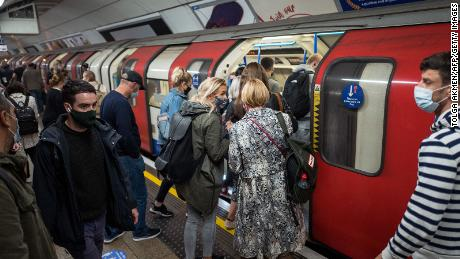 "Commuters wearing masks crowd on to a London tube train on September 23. The city will enter the ""high"" alert level on Saturday, meaning a ban on households mixing indoors."