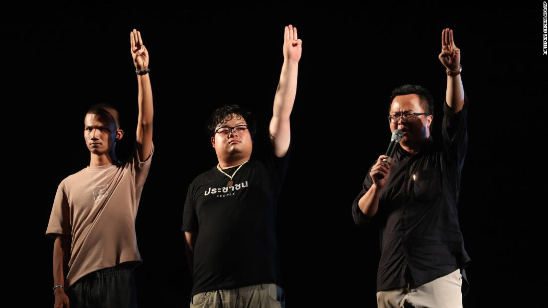 Activists for democracy, from left, Panupong Jadnok, Arnon Nampha, and Parit Chiwarak, raise three-finger salutes on October 15.