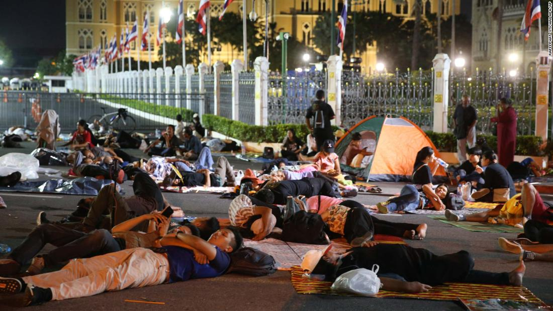 Protesters sleep in front of Government House in Bangkok during a demonstration on October 15.