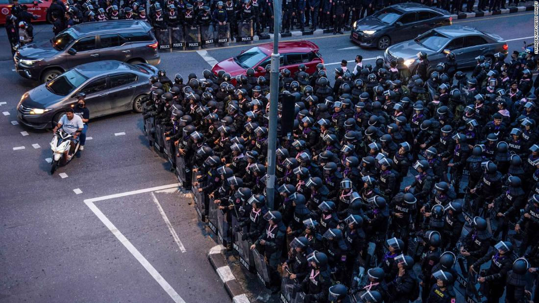 Motorists ride past riot police in Bangkok on October 15.