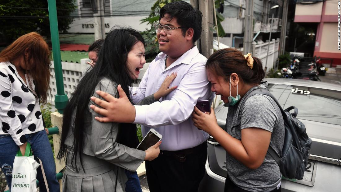 "Pro-democracy activist Bunkueanun ""Francis"" Paothong, center, comforts loved ones before he enters the Dusit Police Station on October 16, to answer charges of harming Thailand's Queen Suthida, two days after protesters nearly obstructed a royal motorcade."