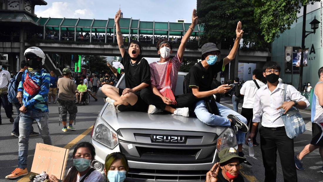 Pro-democracy sitting atop a police vehicle give the three-finger salute, a reference to the Hunger Games movies, which has become a popular symbol of the protests.