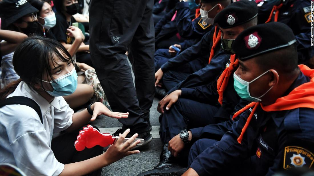 A young pro-democracy protester talks with police during a demonstration in Bangkok on October 15.