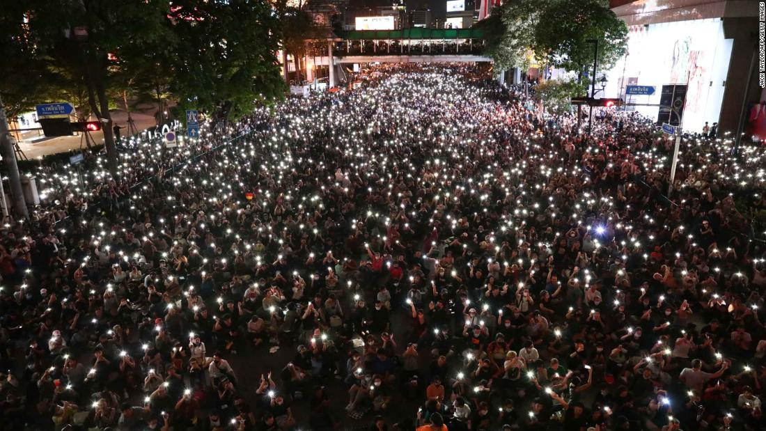 Protesters shine lights from their phones during a demonstration in Bangkok on October 15.