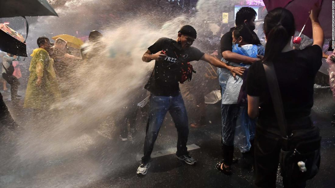 Pro-democracy protesters are blasted by police water cannons on October 16.