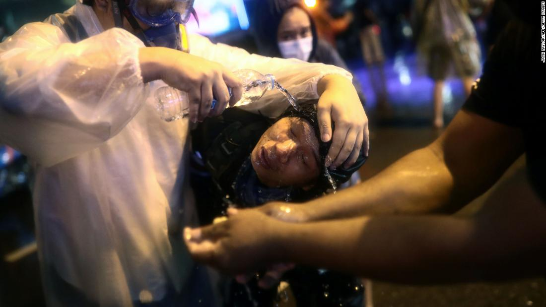 Protesters gather around a fellow pro-democracy activist to wash his face after police fired water cannons laced with pepper on October 16.
