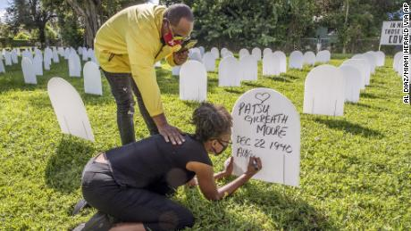 Rachel Moore honors her mother, Patsy Gilreath Moore, by writing her mother's name on a symbolic tombstone at Simonhoff Park in the Liberty City neighborhood of Miami on October 14.