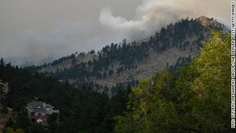 The CalWood fire burns on a hillside sending up a large plume of smoke near Buckingham Park northwest of Boulder.