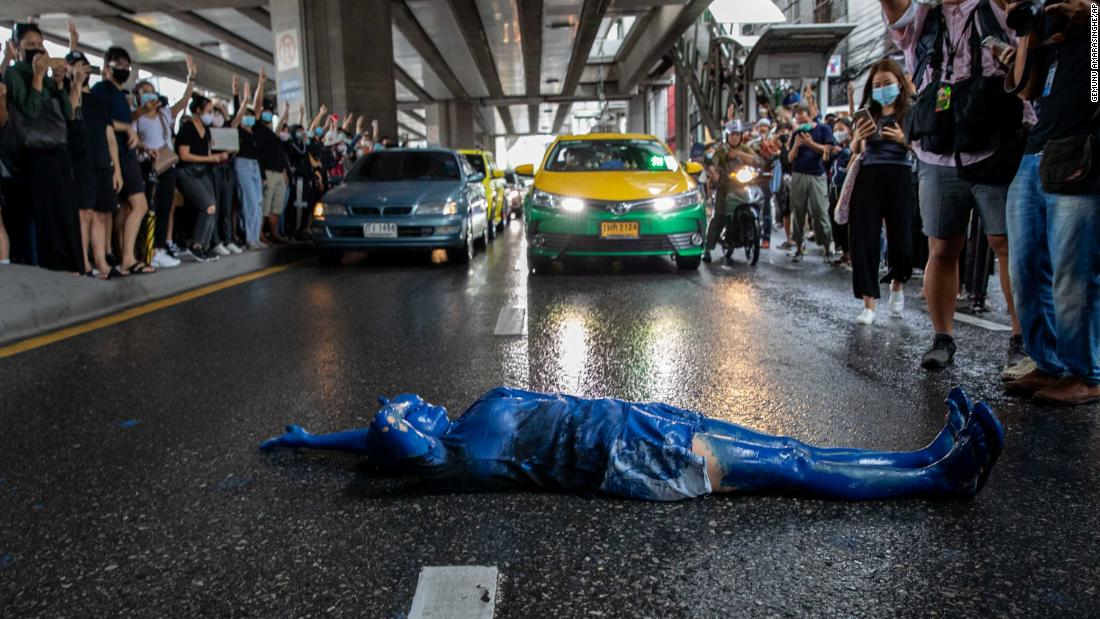 A protester covered in blue paint lies on a road during a protest in Udom Suk, in Bangkok's suburbs, 10月に 17.