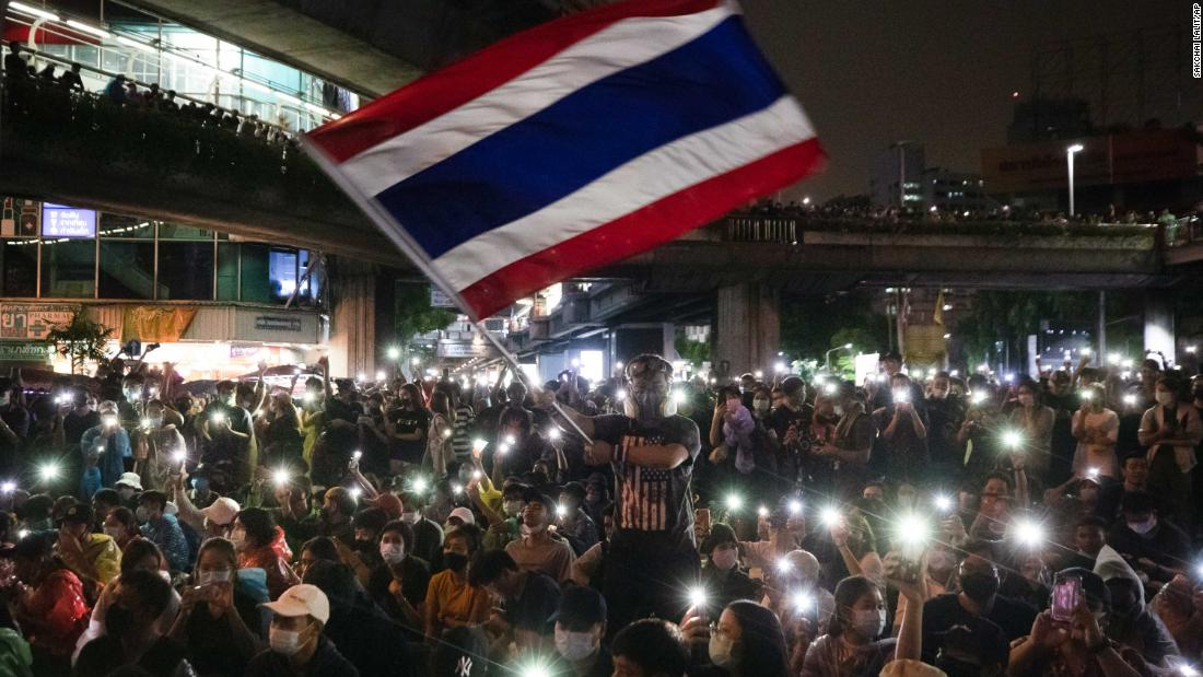 A protester waves Thailand's national flag as others shine their mobile phone lights on October 18.