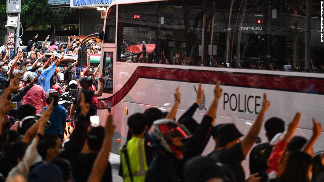 Pro-democracy protesters give the three-finger salute as a police bus passes at Wongwian Yai on October 17.