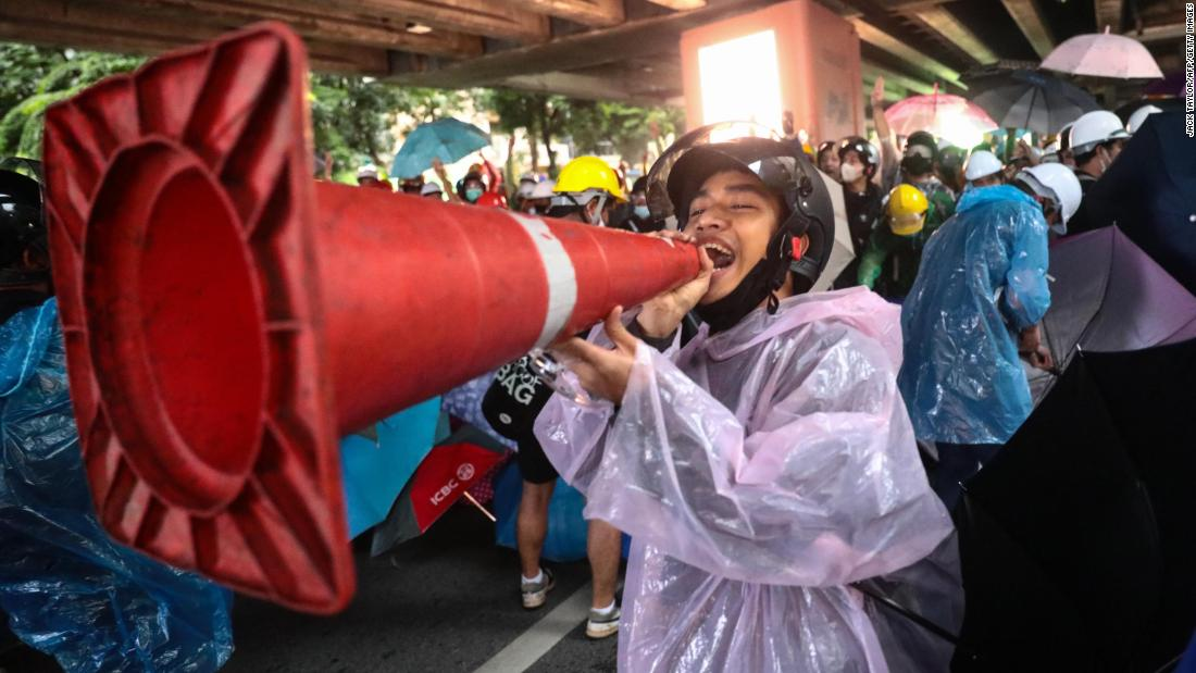 A pro-democracy protester jokingly uses a traffic cone as a loudpspeaker during an anti-government rally at Victory Monument in Bangkok on October 18.