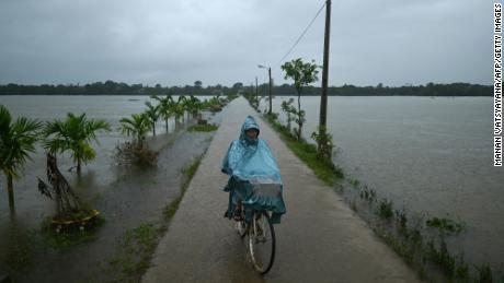 A man rides his bicycle past flood waters during heavy rain showers in Hai Lang district in central Vietnam's Quang Tri province on October 16, 2020.