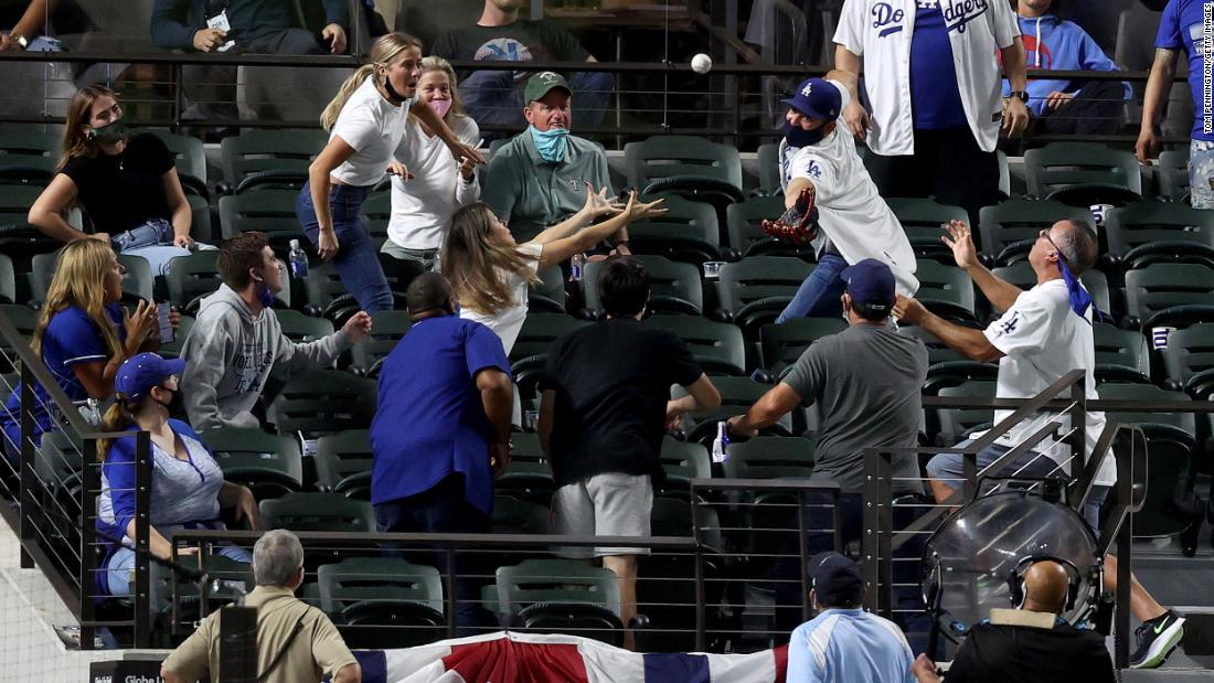 Fans attempt to catch a foul ball.