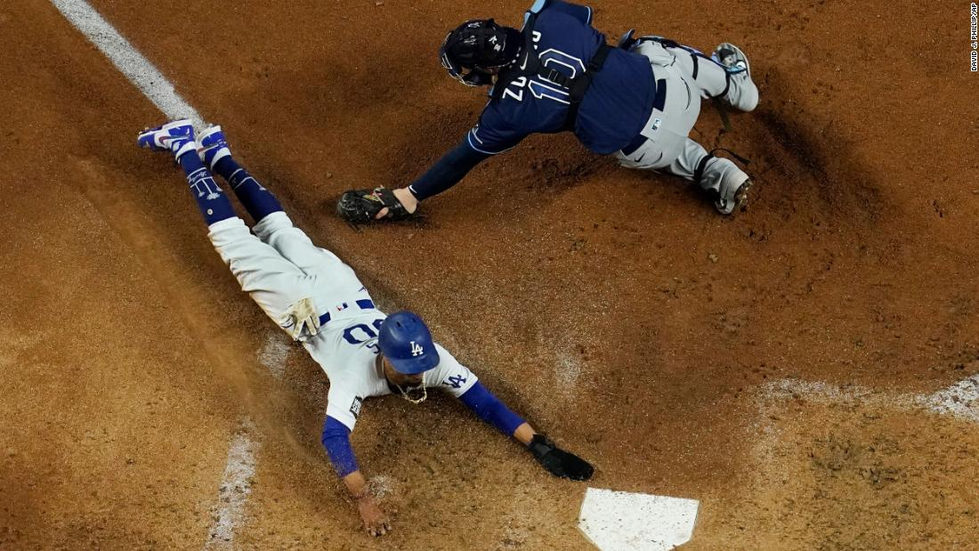 Dodgers outfielder Mookie Betts slides safely into home around the glove of Rays catcher Mike Zunino in the fifth inning.