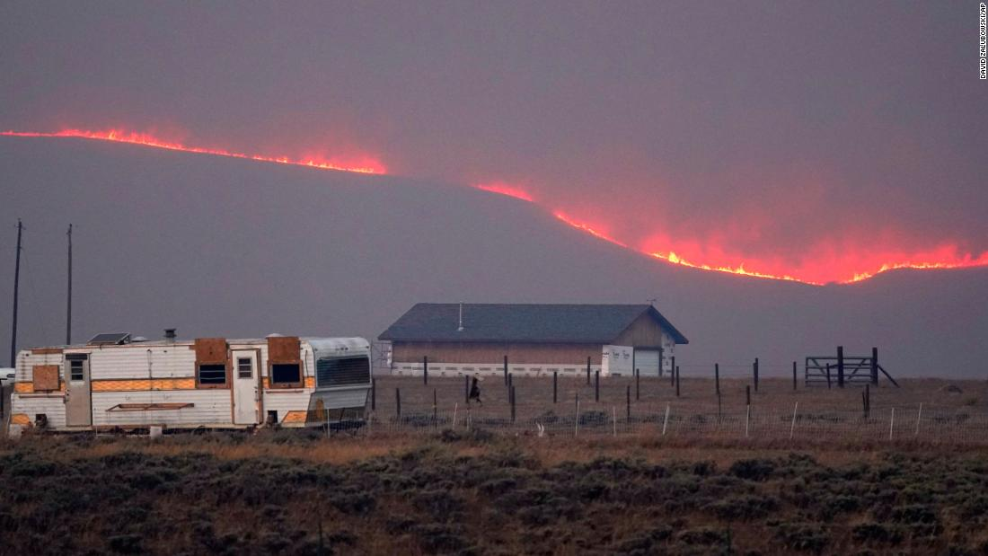 Flames rise from mountain ridges near a farmstead as a wildfire burns near Granby, Colorado, op Donderdag, Oktober 22.