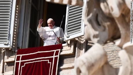 Pope Francis waves to pilgrims gathered in St. Peter's square during his Sunday Angelus prayer on October 25, 2020, at the Vatican.