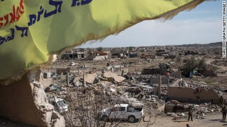 A Syrian Defence Force (SDF) flag flies over the destroyed ISIL encampment on March 23, 2019 in Baghouz, Syria.