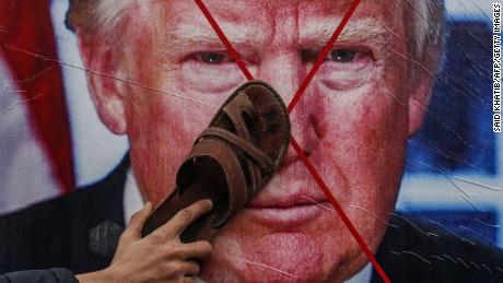 A Palestinian protester holds his sandal against a poster depicting US President Donald Trump during a demonstration against Trump's Middle East peace proposal in Khan Yunis, in the southern Gaza Strip, on February 3, 2020.