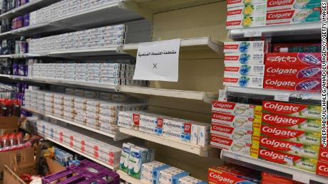 A sign is placed on partially empty shelves at a market, boycotting French goods in Kuwait City, Kuwait on October 24