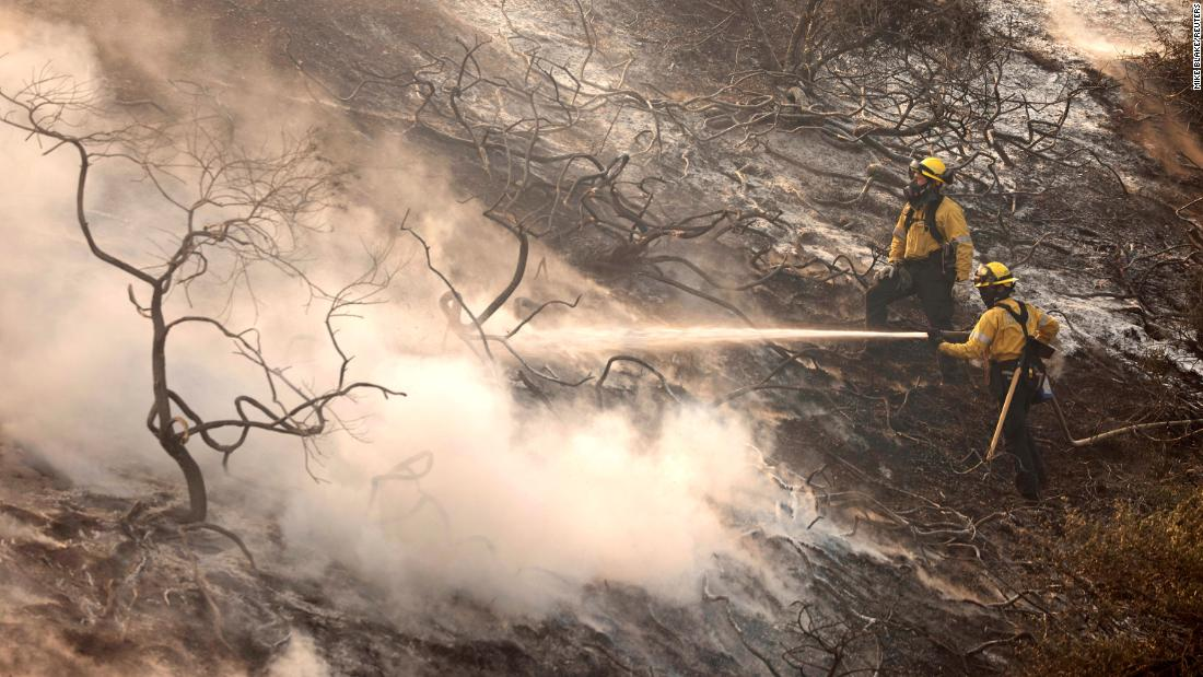 A firefighter uses a hose as the Silverado Fire approaches near Irvine, Kalifornië.