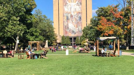 Students sit outside and take a break between classes on the campus of Notre Dame University in South Bend, Indiana on October 6, 2020.