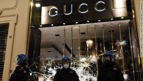 Italian police guard a shattered Gucci store window in Turin on Monday.
