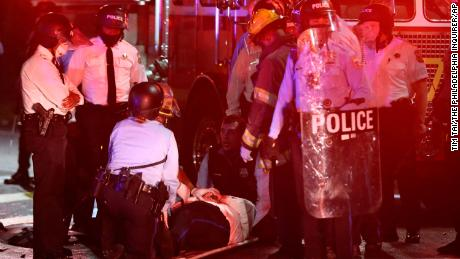 A police officer lies on the ground before being loaded into an ambulance on 52nd Street early on October 27.