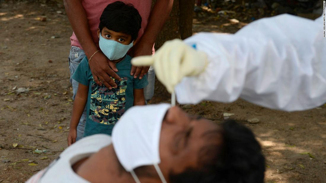 A boy watches as a health worker tests someone for Covid-19 in Hyderabad, India, in ottobre 27.