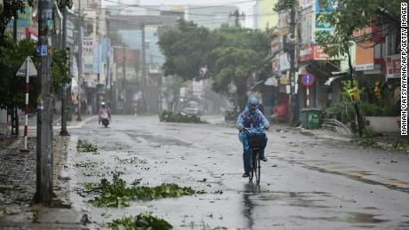 A man rides along a deserted road amid strong winds in central Vietnam's Quang Ngai province on Wednesday Typhoon Molave makes landfall.