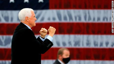 """US Vice President Mike Pence walks on stage at a """"Make America Great Again!"""" campaign event at Oakland County International Airport in Waterford, Michigan, on October 22, 2020."""