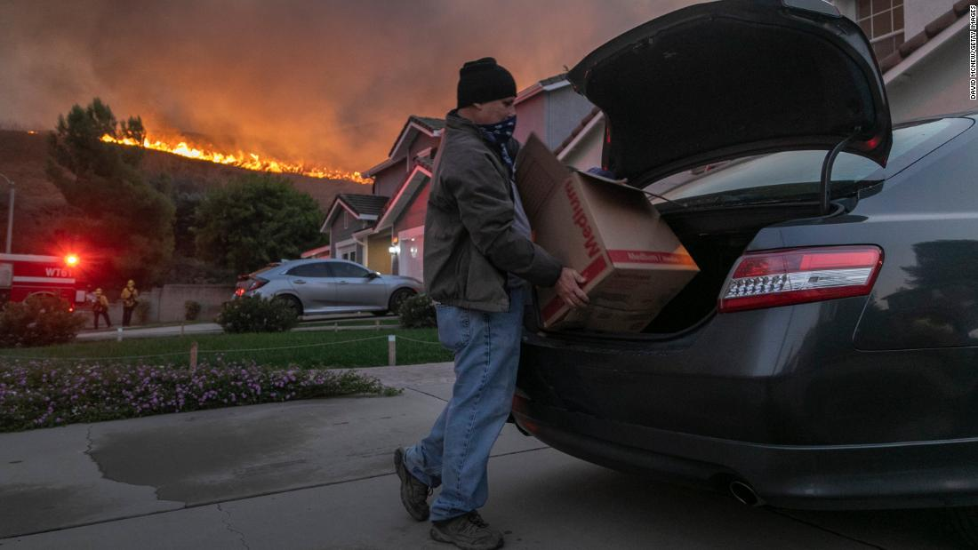 A man evacuates his home as flames from the Blue Ridge Fire approach in Chino Hills, Kalifornië, op Dinsdag, Oktober 27.