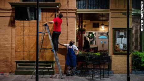 General manager Gaige Rodriguez, 剩下, and cook Michael Dillon board up windows at Pere Antoine Restaurant in New Orleans in preparation for Hurricane Zeta, which made landfall Wednesday.