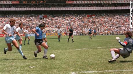 Maradona runs past English defender Terry Butcher (left) on his way to dribbling goalkeeper Peter Shilton (right) and scoring his second goal against England in the World Cup in 1986.