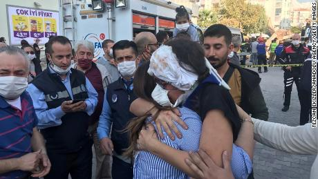 A wounded woman hugs her relative after being rescued from debris of a building in Bornova district of Izmir on Friday.