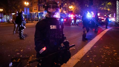 Vancouver police stand guard as a tense standoff took place after Friday's vigil.
