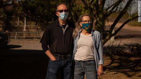 Ann Whitmire, right, and her husband William are pictured outside their Phoenix home. Ann, who contracted the coronavirus in June, considered voting for Donald Trump this year until she heard the President make a series of false claims about pandemic.