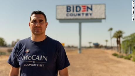 Yasser Sanchez stands in front of a billboard he funded off the side of Interstate 10 in Phoenix.