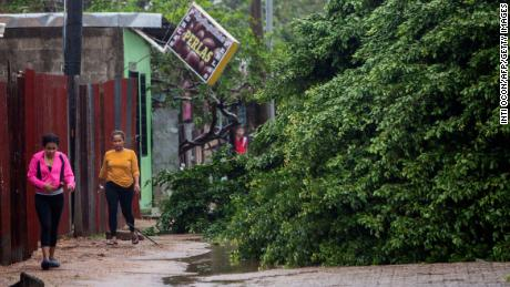 Women walk next to fallen trees Tuesday morning in Puerto Cabezas, Nicaragua, after winds from Hurricane Eta raked the area.